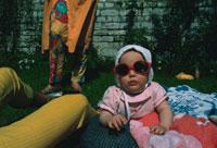 屋内に座るサングラスをかけた赤ちゃん