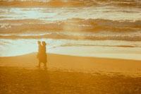 海岸を歩くカップルのシルエット(オレンジ色)