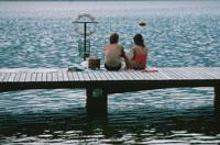 海の桟橋に座るカップルの後姿
