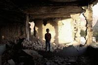 破壊された建物の中に立つ子供