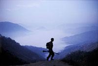 霧の谷を見下ろす山を歩く兵士