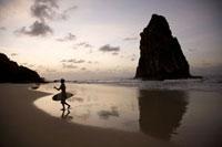 奇岩の有るビーチを歩くサーファーのシルエット 02265038021| 写真素材・ストックフォト・画像・イラスト素材|アマナイメージズ