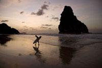奇岩の有るビーチを歩くサーファーのシルエット 02265038022| 写真素材・ストックフォト・画像・イラスト素材|アマナイメージズ