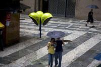 公衆電話のある広場を傘をさして歩くカップル