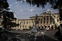 割れたガラスに映る市中心の広場にあるスターリン像