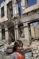 破壊された建物の前を歩く少女