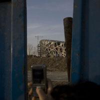 携帯電話で北京国家体育場を撮影する人