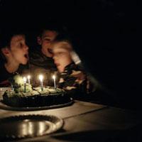 誕生日のケーキのロウソクを吹く子供達