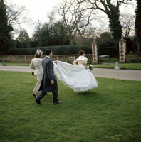 ウェデイングドレスの裾を持って歩く人達と花嫁