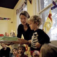誕生パーティーとケーキを持つ母親