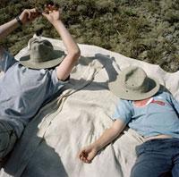帽子で日よけをして横になる兄弟