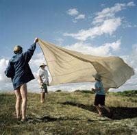 草原で布を風に靡かせる母子