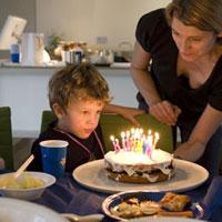 ロウソクが乗ったバースデーケーキを見る子供