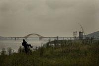 橋のかかる川辺に自転車で来た人