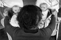 双子と手を繋ぐ母親の後姿
