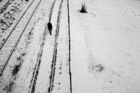 雪が積もった線路を歩く人物点景
