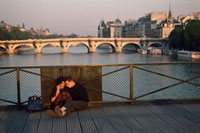 Couple on the Pont des Arts looking toward the Pont Neuf