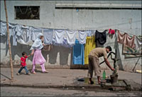 水を汲む男性と通りを歩く親子