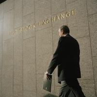 証券取引所を通り過ぎるビジネスマン