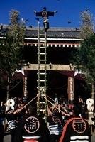 祭で賑わう人々とはしごの上の男性