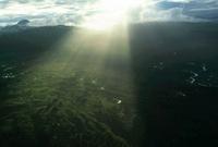 雲の切れ間から緑地へ射し込む太陽
