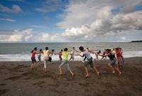 浜辺で輪になって踊る女性達