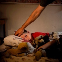 ベッドの少年の頭をさする大人の手