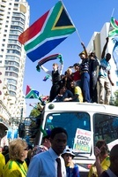 南アフリカの国旗を掲げて車の上で叫ぶ男性
