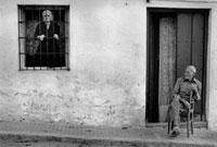 玄関前の椅子に座る男性と格子窓の老人