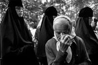 涙を拭う老人と宗教服の人々