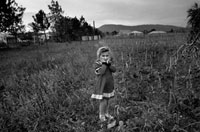 頬に手をやる草野原に立つ少女