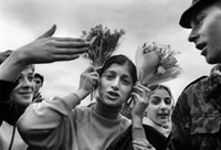 人に囲まれる花束を持つ女性