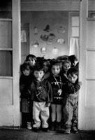 部屋の敷居から見つめる子供達