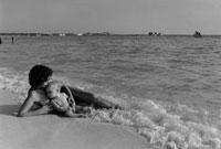 波打ち際で横になる母親と赤ちゃん