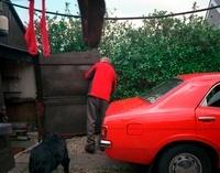 赤い車と赤いジャケットの男性