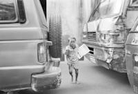 車の間を走る新聞売りの子ども
