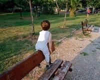 公園のベンチで遊ぶ男児