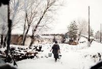 雪の中バケツを運ぶ女性