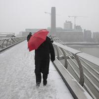 雪の中橋を渡る男性