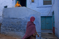 青い家の前を通り過ぎる赤いサリーの女性