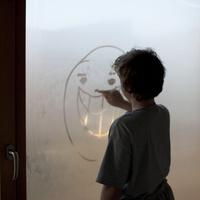 ガラスに絵を描く少年