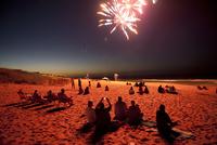 浜辺で花火を観る人々