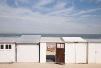 浜辺に建ち並ぶ小屋と日光浴をする男性