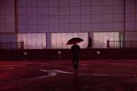 夕暮れ時、傘をさして歩く男性