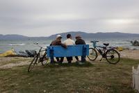 海の見えるベンチに座る3人の男性
