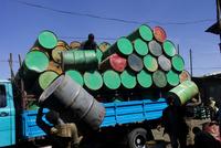 市場でドラム缶を積むトラック