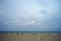 浜辺でサッカーに興じる人々