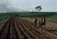 鉄鋼工場を背に、畑を耕す農夫