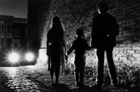 GB. London. Hackney. Night silhouette of couple with child, shot in Hackney.