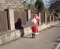 GB.The home of Colin NAYLOR.  Christmas. Father Christmas delivering the presents. 1995.